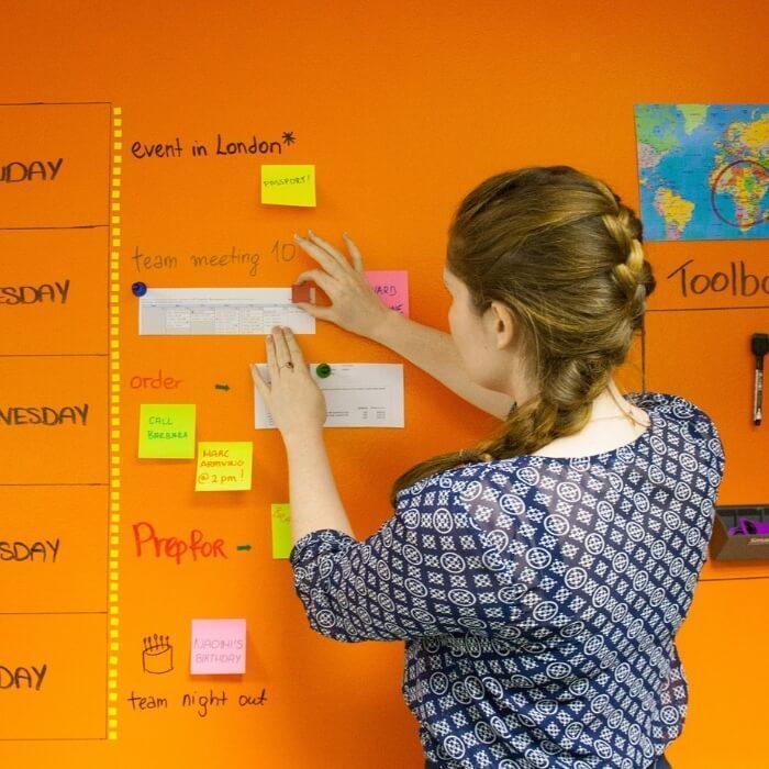 Frau-haelt-ein-Papier-mit-Magnet-an-Wand-mit-Smart-magnetischer-Whiteboard-Farbe-Transparent-gestrichen