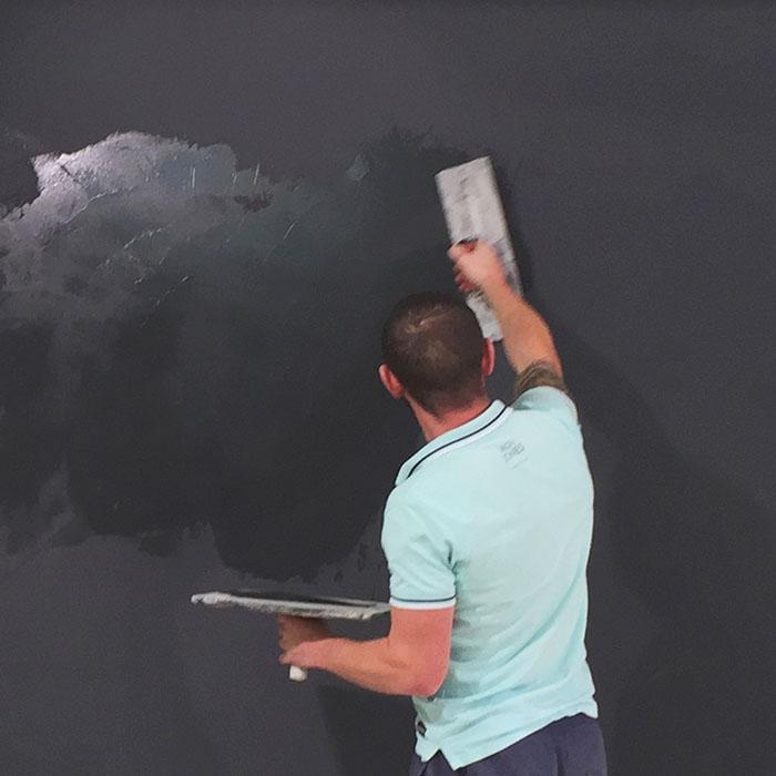 Handwerker trägt Smart Magnetputz auf die Wand auf