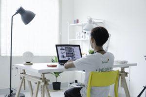 Mensch sitzt vor einem Laptop und arbeitet